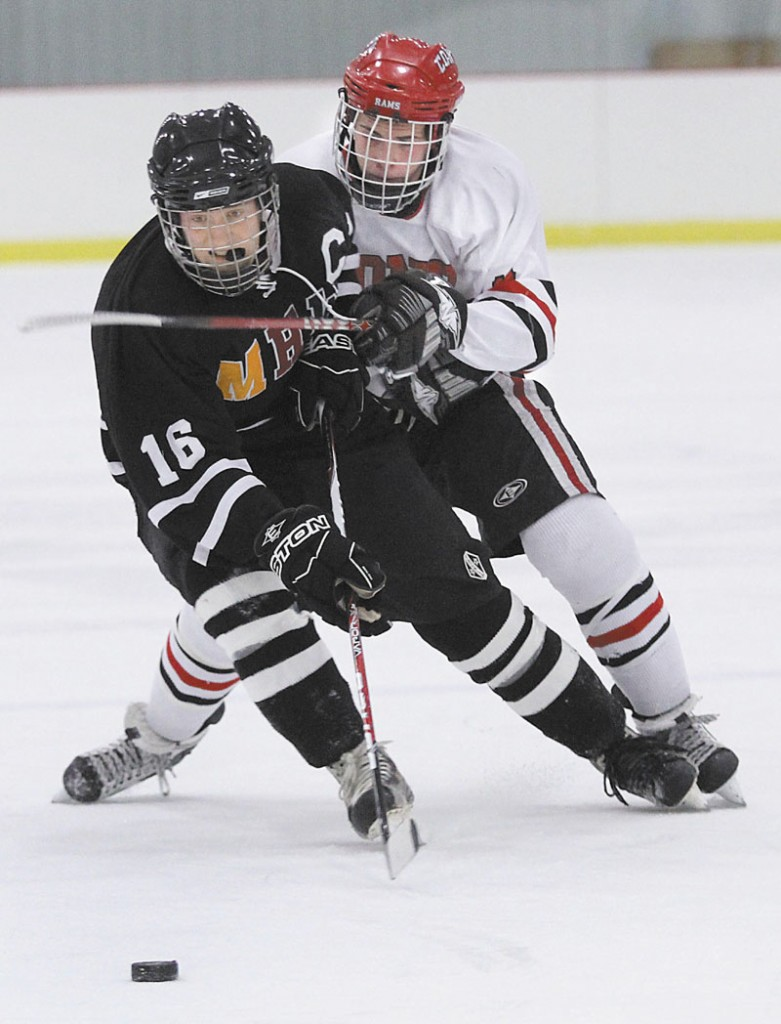 A STICKING POINT: MHW forward Tyler Bryant (16) battles for the puck with Cony High School's Austin Davis during the first period of Monday's game in Kents Hill.