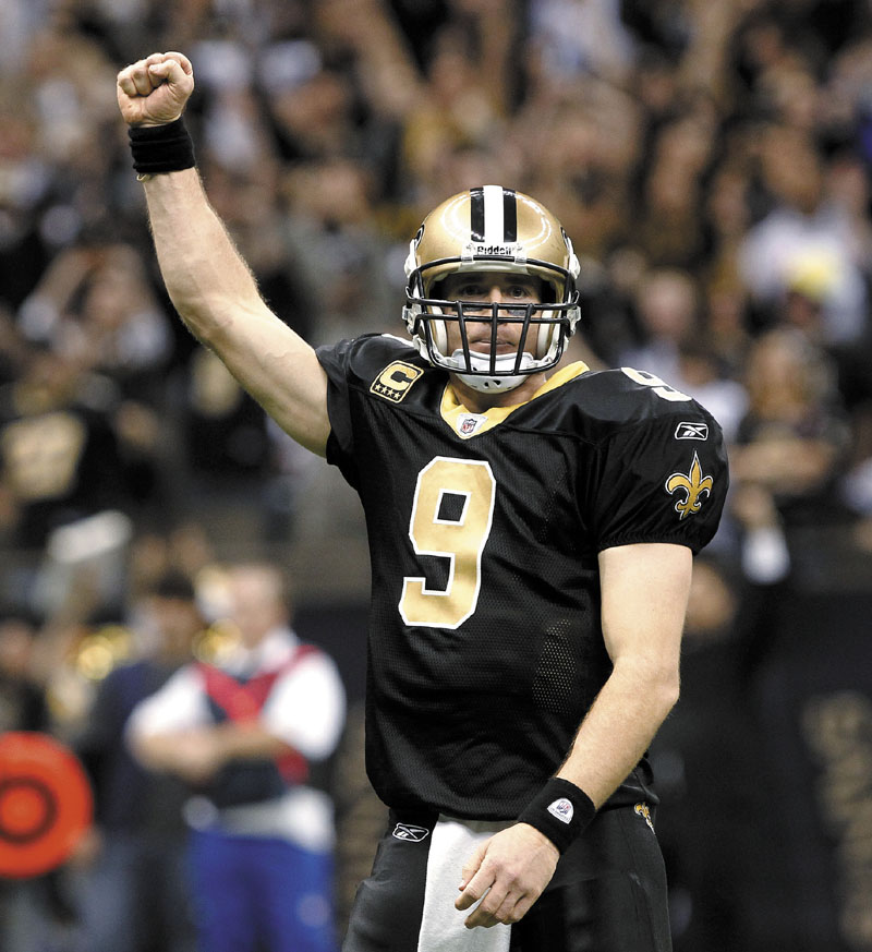 RECORD SETTER: New Orleans Saints quarterback Drew Brees celebrates after throwing a touchdown pass and breaking the NFL single-season record for passing yardage held by Dan Marino on Monday in New Orleans. NFLACTION11;