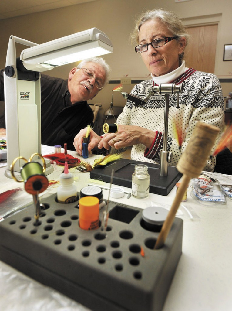 LEARNING THE TRICK OF THE TRADE: Evelyn King and her Mickey Finn get some much-appreciated attention from Lane Soltesz, a fisherman for 40 years. Both of them are benefiting from fly tying class.