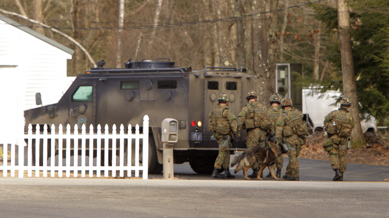 A SWAT team waits behind their vehicle at a house on New Dam Road in Sanford this morning. Police questioned some of fugitive David Hobson's relatives who live along the road and searched an area nearby where they found clothing and medical supplies.