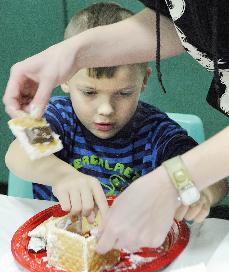 STICKY ENGINEERING: Kindergartener Trysten Legassie and his mother, Samantha Cushing, build and decorate a train from graham crackers, frosting and candy during a Math Mania event Thursday at Laura E. Richards School in Gardiner. About 150 parents and kids attended the event, which featured a pizza dinner after math games and was held to help support math concepts the students have been learning, according to Principal Karen Moody.