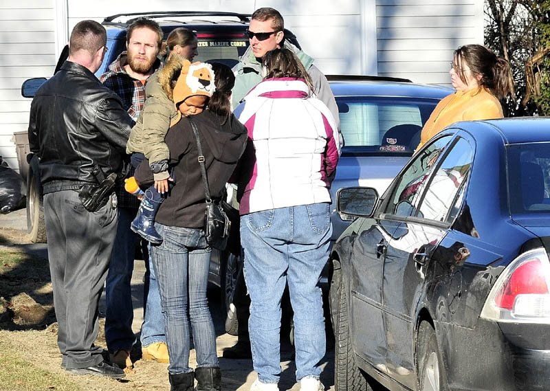 Maine State Police Detective Christopher Tupper, left, and Waterville Detective Lincoln Ryder, at right, speak with Justin DiPietro after he arrived at his home on Violette Avenue in Waterville on Sunday as an extensive search was under way at his home and the neighborhood for his 20-month-old daughter, Ayla Reynolds, who has been missing since Friday.