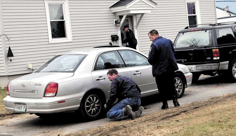 Staff photo by David Leaming LOOKING FOR EVIDENCE: Maine State Police Detective Scott Bryant watches as a tow truck operator hooks on to the first of two vehicles that were taken from a home at 29 Violette Ave. in Waterville on Monday. The home has been subject to an intense investigation for 20-month-old Ayla Reynolds who has been missing since last Friday. The girl and her father Justin DiPietro live at the home.