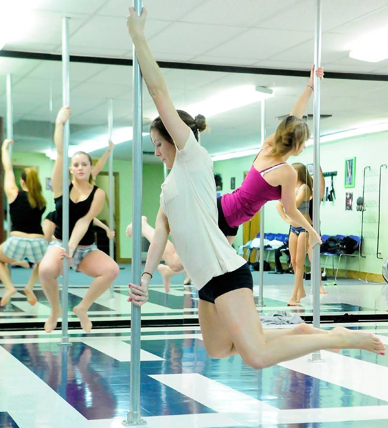 HANGING AROUND: Sarah Stetson, left, Molly Hendsbee and Tammy Poulin hang off their pole during a pole fitness class on Wednesday night at Heaven-Lee Heights Inc. at 553 Maine Ave., Farmingdale.