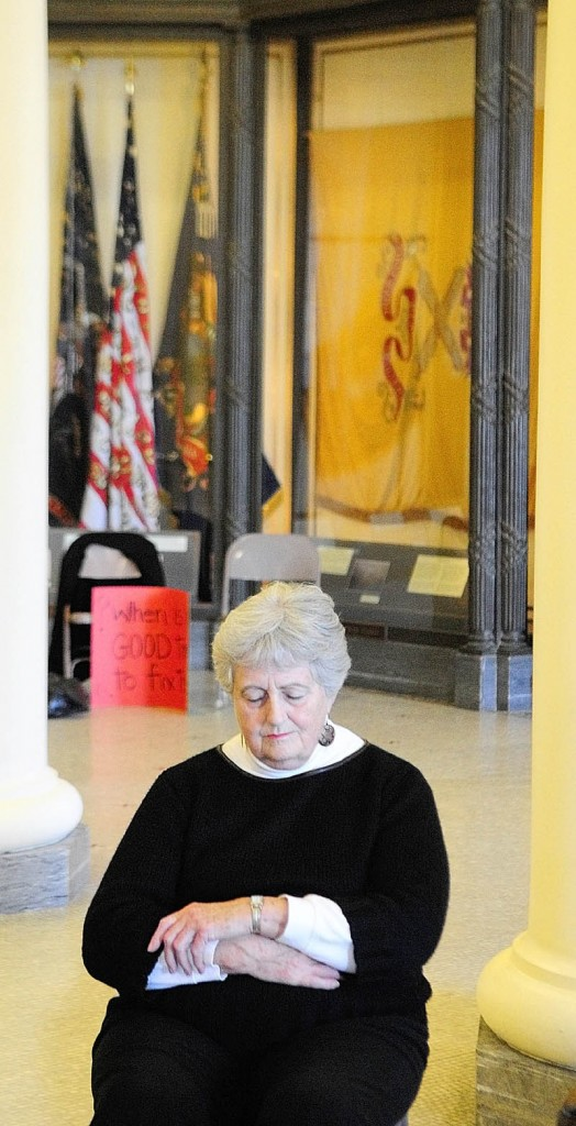 SOLEMN MOMENT: Denise Dreher, of Biddeford, prays in the State House's Hall of Flags on Friday in Augusta. The Maine Council of Churches held a prayer vigil up the hallway from where a legislative committee held a three-day hearing on the Department of Health and Human Service's supplemental budget.