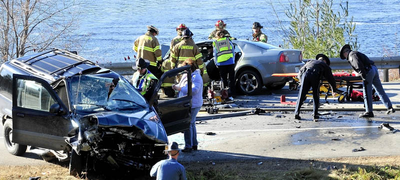 HECTIC SCENE: Police and fire officials investigate the chaotic scene of a head- on collision of two cars on U.S. Route 2 near the eddy in Skowhegan on Thursday. Both seriously injured drivers of each vehicle were pinned inside.