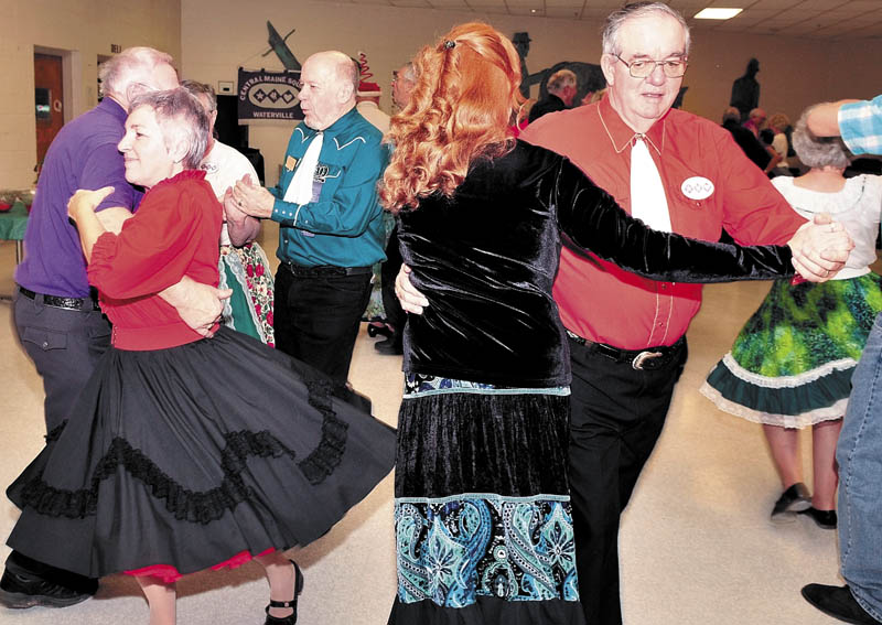 Barb Gilbert, left, of Winslow and her husband Dick, far right, dance during a recent square dance at the Waterville Junior High School.