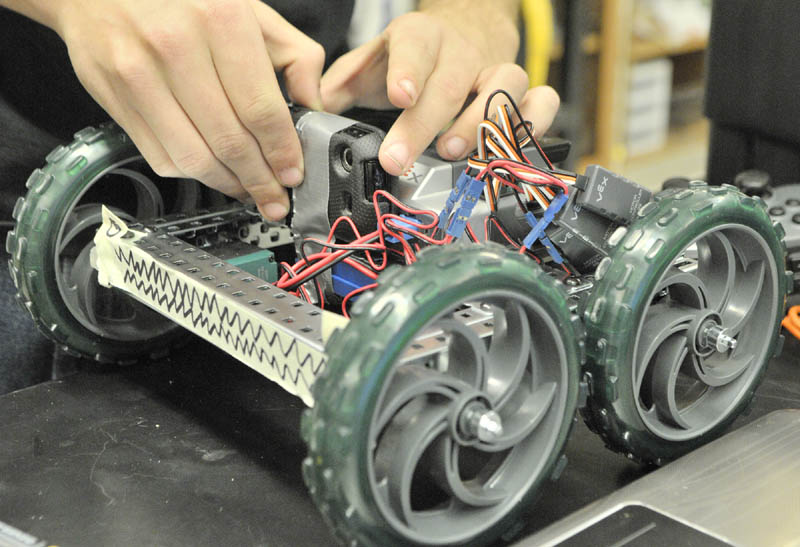 Cody Jackson tapes a cell phone onto a robot so that it could shoot a video of it running over the obstacle course on Thursday morning at Cony High School in Augusta.