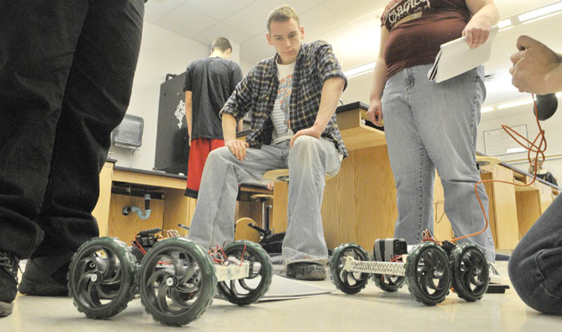 Brandon McCutcheon, center, watches as his classmates run their robots on Thursday morning at Cony High School in Augusta.