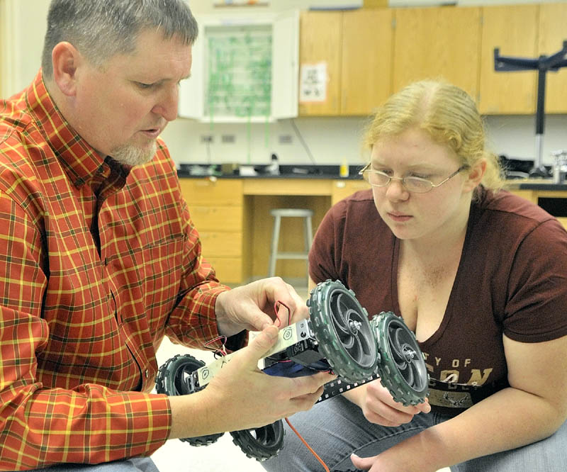 Science teacher Jeff DeJongh, left, and student Brittany Manson check the wiring on a malfunctioning robot on Thursday morning at Cony High School in Augusta.