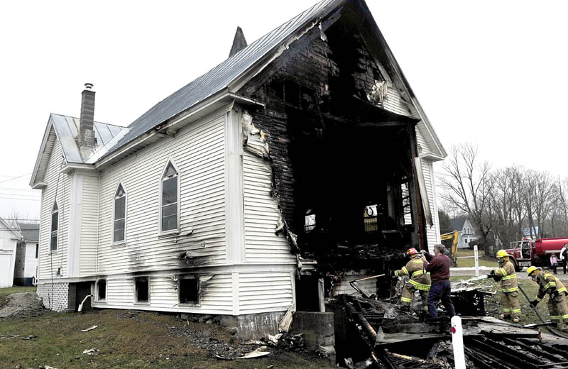 Staff photo by David Leaming REMAINS: Firefighters extinguish smoldering wood as Stu Jabobs of the state Fire Marshals Office photographs the scene near the back side of the Thorndike Congregational Church after fire destroyed the century old church early Wednesday. Investigators determined the cause was an electrical malfunction. Church member Patty Banker later said the church will be rebuilt.