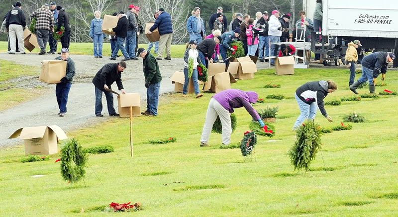 A SIMPLE GESTURE: Volunteers unload the truck and start to lay wreaths on markers Saturday morning at the Maine Veterans' Memorial Cemetery on Mount Vernon Road in Augusta. Volunteers with the Wreaths Across America project also laid wreaths on graves there and at Togus National Cemetery.