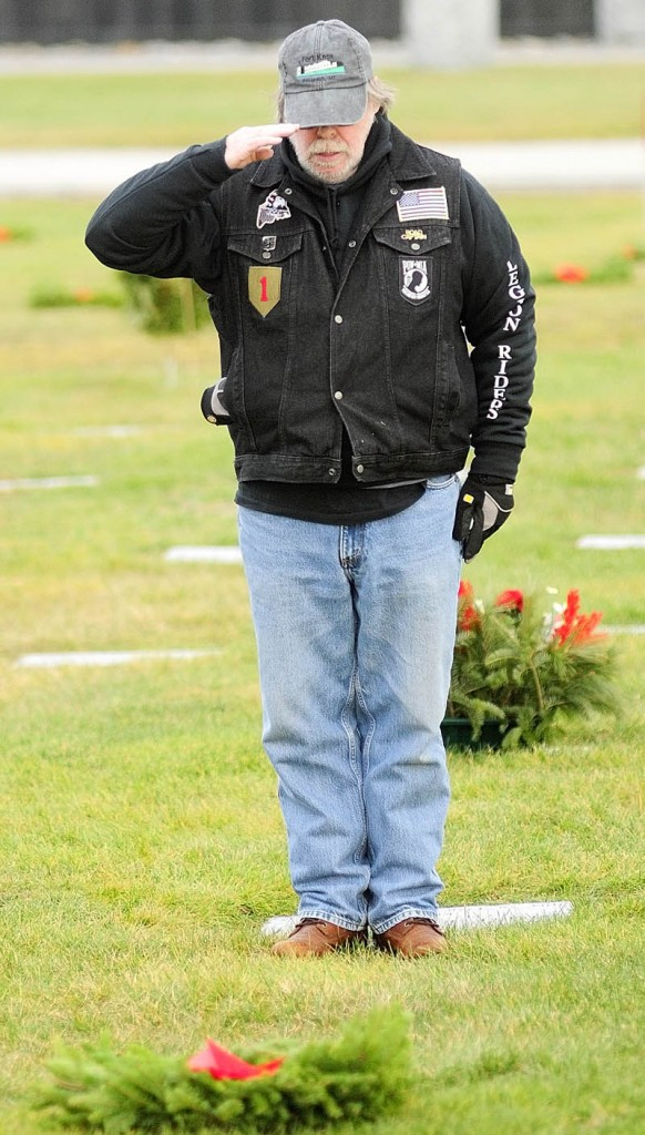 SALUTE: Gary Orcutt, of Norridgewock, salutes after placing a wreath on a veteran's grave Saturday at Maine Veterans' Memorial Cemetery on Mount Vernon Road in Augusta.