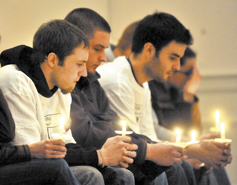 Tears stream down the face of Justin DiPietro, left, during a candlelight vigil for his missing daughter, Ayla Reynolds, at First Congregational Church in Waterville on Tuesday.