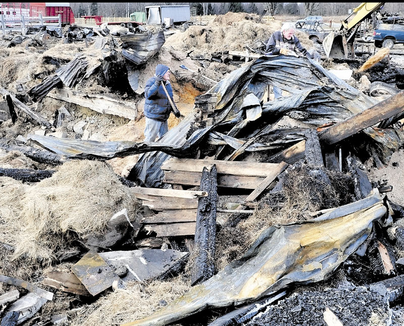 SALVAGE: Bill Thrasher, left, and his brother Jim salvage sawdust from the ruins of a barn at the Knowlton Corner farm in Farmington on Wednesday.