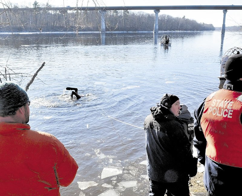 INTO THE COLD: A diver heads back underwater as a search boat motors above the Carter Memorial Bridge in the Kennebec River as state police and the Maine Warden Search conducted an extensive search of the river for signs of missing toddler Ayla Reynolds on Wednesday.