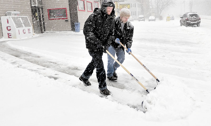 TEAMWORK: Dave Huntington, left, and Brad Hayden shovel snow off the parking lot at Jokas store in Waterville on Thursday.