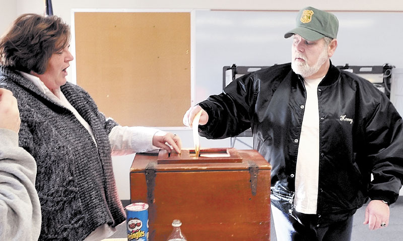 CIVIC DUTY: Starks resident Kenneth Laux casts his ballot as ballot clerk Tracy Quimby monitors voting at the Starks Community Center on Tuesday. Residents voted to secede from School Administrative District 59 and send students to Mt. Blue's school district.