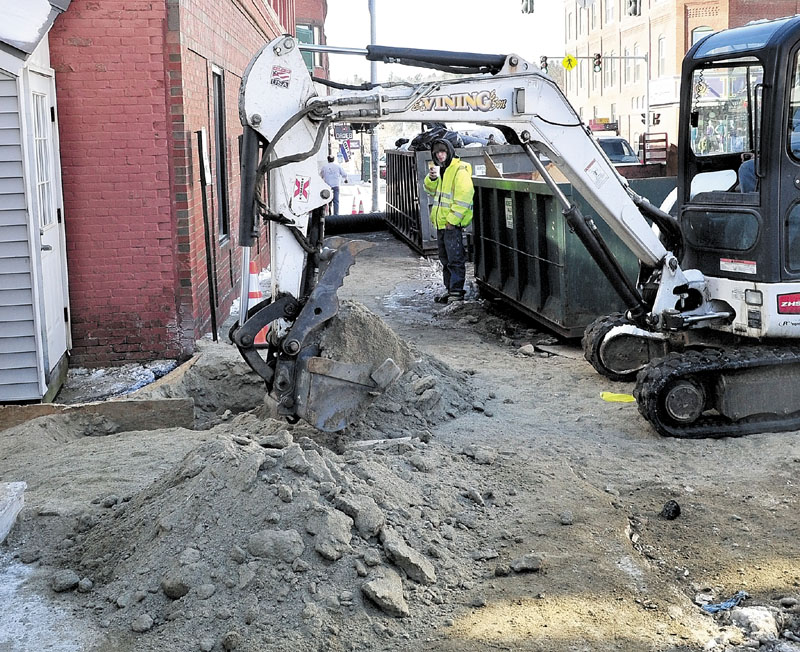 DIG IT: An excavator operator with E.L. Vining & Sons on Monday digs up the sidewalk where a water main pipe broke. The water filled the basement of TD Bank and Trask Jewelers in downtown Farmington, causing extensive damage to both businesses.