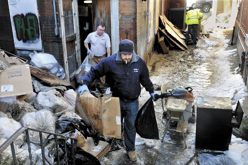 CLEAN UP: Workers carry water-soaked debris through an ice-covered alley behind Trask Jewelers in Farmington on Monday while cleaning up after a water main break.