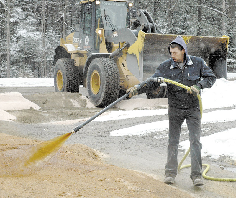 GREEN SALT: Bob Corrigan of the Skowhegan Highway Department sprays Ice B'Gone, a road de-icer made from high-sugar beet molasses, on road salt at the town sand-and-salt yard recently. Road Commissioner Greg Dore hopes it will save money on winter road budgets.