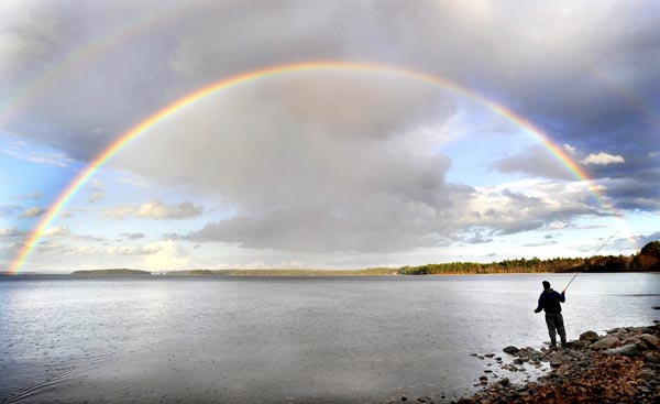 In this 2010 photo, fly fisherman Stephen Sparaco is framed by a rainbow as skies clear over Sebago Lake in Standish.