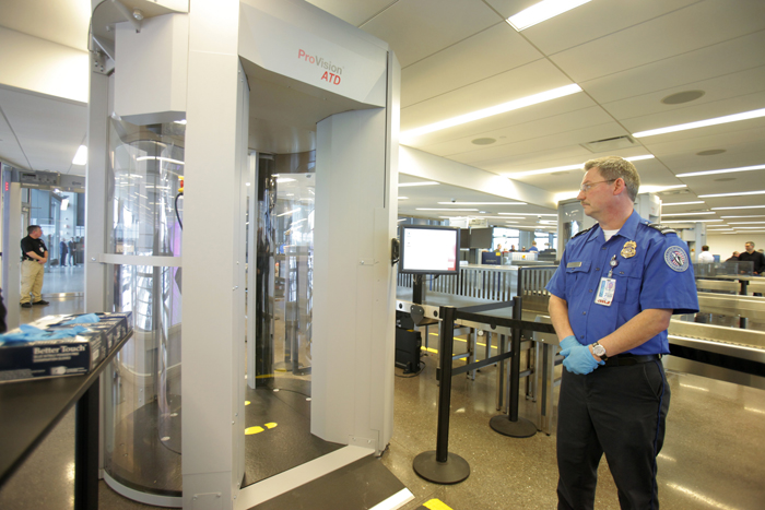 TSA employee Dale Tucker stands near one of three new passenger screening devices in the security checkpoint area at jetport today. The devices screen for metallic and nonmetallic items using electromagnetic waves.