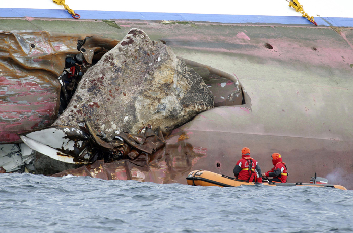 Firefighters on a dinghy look at a rock emerging from the side of the luxury cruise ship Costa Concordia off the island of Giglio, Italy.