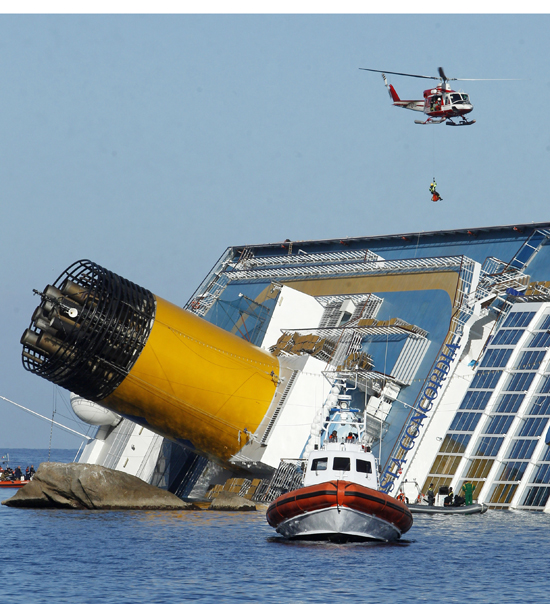 An Italian fireman descends from a helicopter to the Costa Concordia today.