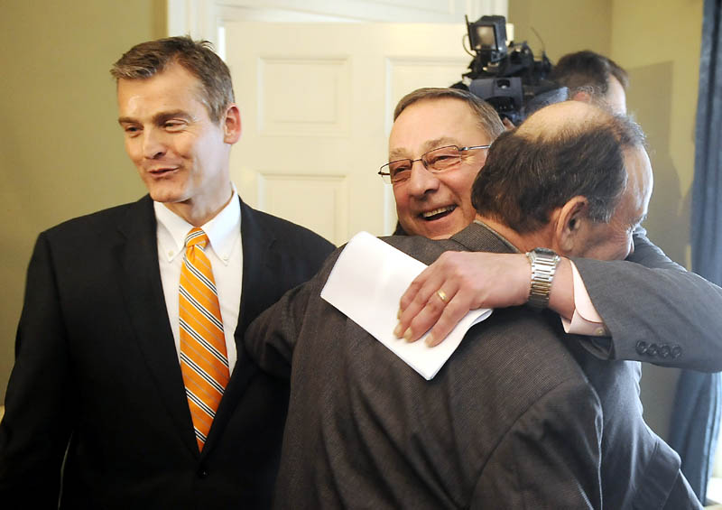 Gov. Paul LePage hugs Bill Alfond on Monday in Augusta after announcing that the Harold Alfond Foundation will give $10.85 million to the Maine Community College System and the Good Will-Hinckley school. Alfond was joined by Good Will-Hinckley President Glenn Cummings, left. The donation will enable the expansion of Kennebec Valley Community College in Fairfield.