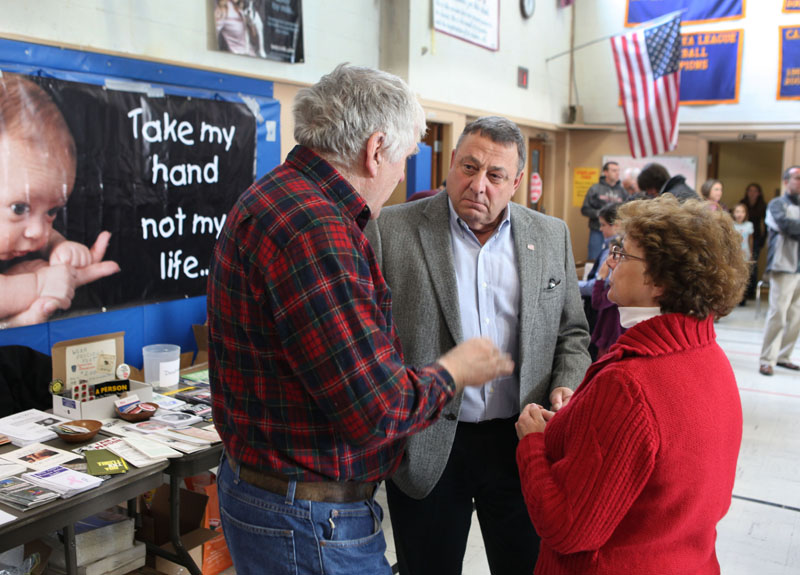 """Gov. Paul LePage, center, speaks with Rep. Paul Davis, R-Sangerville, left, and his wife Patty Davis, rightt, on Saturday at an anti-abortion rally in Augusta as part of the annual """"Hands Around the Capitol Rally and March."""""""