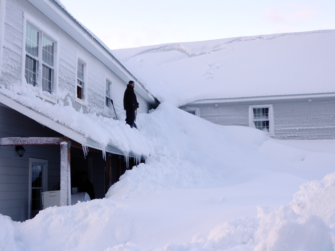 A Jan. 7, 2012, photo provided by the Alaska Division of Homeland Security and Emergency Management shows a man standing on a house buried in snow in the fishing town of Cordova, Alaska.