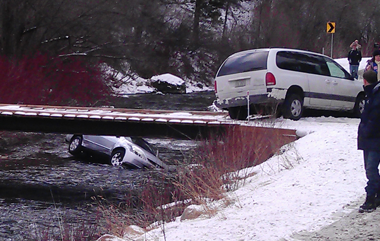 A photo provided by Chris Willden shows a car in the Logan River in Utah, after the car was flipped upright by rescuers who saved three children trapped in the car. The car plunged off an embankment into the river and Willden shot out the car's window with a handgun and cut a seat belt to help free the children after the accident.