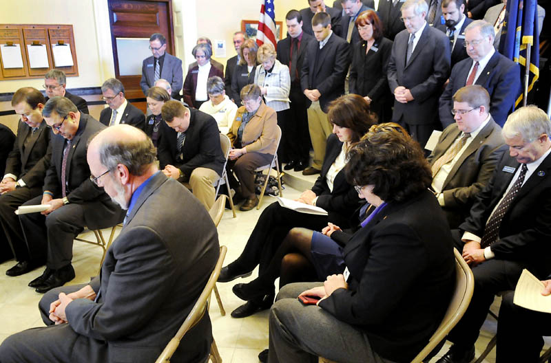 Legislators and state officials bow their head in prayer Tuesday during the Maine Call to Prayer event at the State House. Senate President Kevin Raye. R-Raye, front row left, Governor Paul LePage and Speaker of the House Robert Nutting, R-Oakland, signed the call to prayer document along with several legislators.