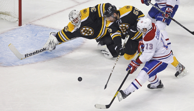 Bruins goalie Tim Thomas dives to make a save on a shot by Canadiens left wing Mike Cammalleri in the first period of their game in Boston on Thursday. At center is Bruins defenseman Johnny Boychuk.