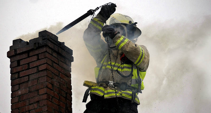 West Gardiner Fire Chief Chris McLaughlin pulls a chain up a chimney on fire Thursday in West Gardiner. Firefighters from West Gardiner and Gardiner worked for an hour at extinguishing the blaze on High Street.