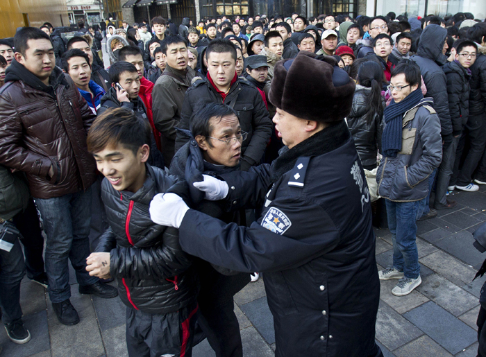 A policeman drags away people who refused to leave the Apple Store in Beijing today after Apple closed the store.