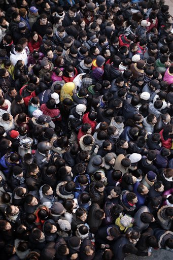 In Shanghai, hundreds of customers queue up to purchase a new smartphone iPhone 4Si.
