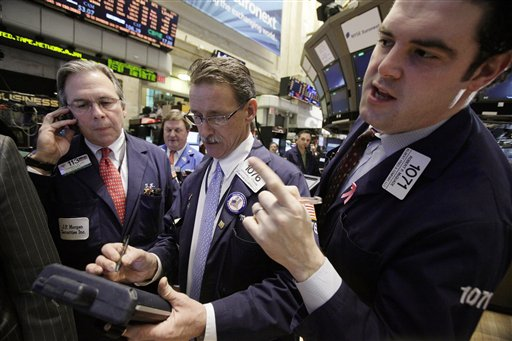 In this Jan. 25, 2012 photo, traders Thomas Kay, left, Marshall Ryan, center, and Robert McQuade work on the floor of the New York Stock Exchange. (AP Photo/Richard Drew)