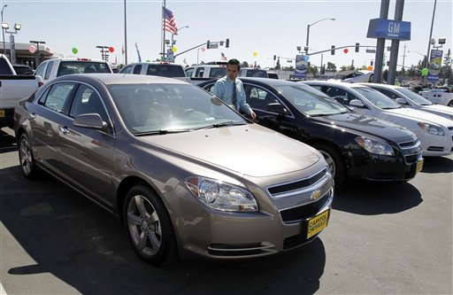 Chevrolet Malibus are lined up at a car dealership in San Jose, Calif., recently. Much of the fourth-quarter growth was powered by a 14.8 percent surge in sales of autos and other long-lasting manufactured goods.