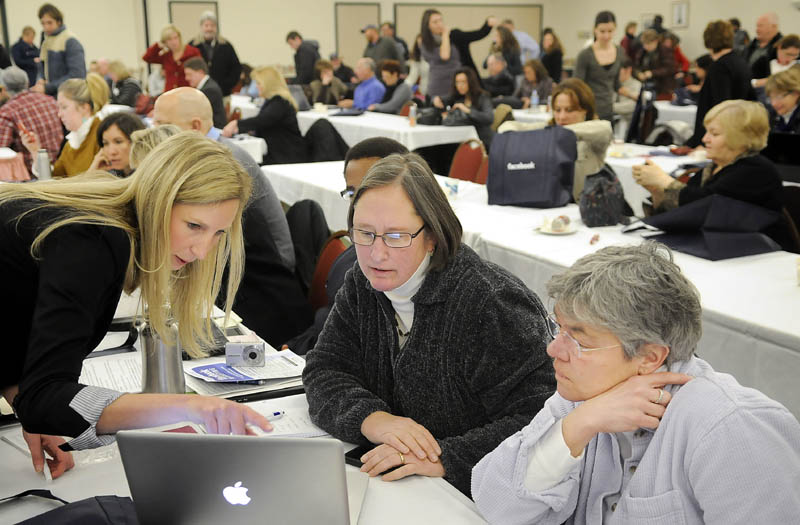 TECH SUPPORT: Facebook employee Kirsten Bury, left, helps Sandy Gnidziejko, center, and Ellen Heath arrange a page for their Biddeford business, Little River Antiques and Collecting, during a Tuesday forum by the internet social networking business in Augusta.
