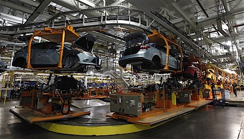 In this Dec. 14 photo, Ford Focus vehicles move on the assembly line at the Ford Michigan Assembly plant in Wayne, Mich. U.S. factories roared to life in December, creating sharply more goods to meet strong demand for business equipment, materials, vehicles and energy. (AP Photo/Paul Sancya)