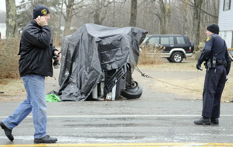CRASH SCENE: Gardiner Police Chief James Toman, left, and officer Dan Murray investigate a rollover accident Saturday that took the lives of two men and injured a third on U.S. Route 201 in Gardiner. The accident occurred after 8 a.m. in icy conditions, according to Toman. Dennis Kay, 62, of Gardiner and Carlton Norwood, 25, of Pittston, died at the scene.
