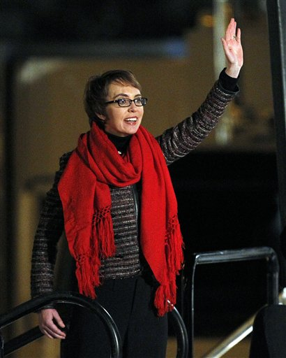 Giffords waves at the start of the Jan. 8 memorial vigil remembering the victims and survivors one year after the Arizona congresswoman was wounded in a shooting that killed six in Tucson, Ariz.