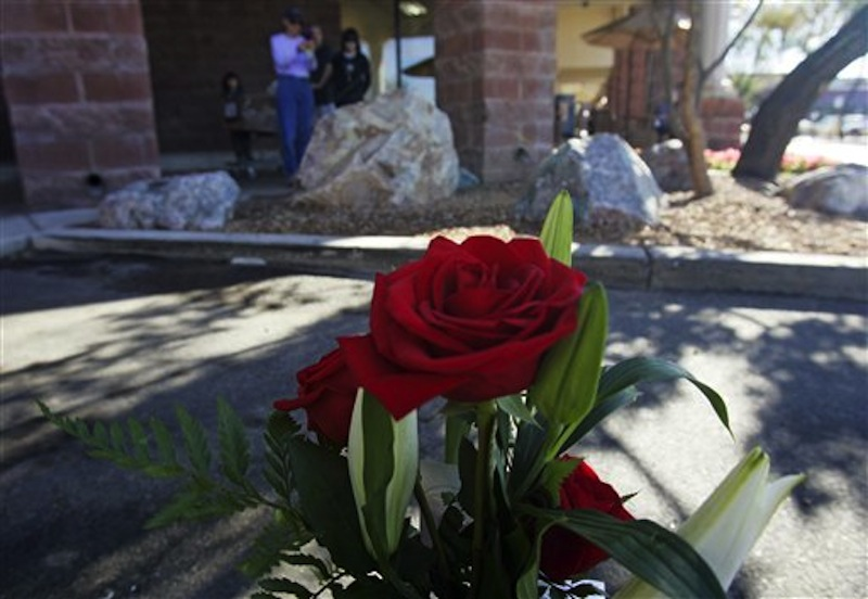 People gaze at a small memorial plaque on a rock at the Safeway market on Saturday, Jan. 7, 2012, to commemorate the victims of the mass shooting on Jan. 8, 2011, in Tucson, Ariz. The one-year anniversary of the shooting of Rep. Gabrielle Giffords in the parking lot of the grocery store is Sunday. Arizona is marking the event with a series of events, including community-wide bell-ringing at the moment of the attack, speeches on behalf of the victims, and an evening candlelight vigil that Giffords will attend. (AP Photo/Arizona Daily Star, Rick Wiley)