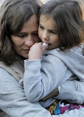 Ina Menzl, left, hugs her daughter, 4-year-old Rebecca Kraft, on Sunday outside the Safeway grocery store where U.S. Rep. Gabrielle Giffords, D-Ariz., was shot one year ago during a shooting spree that left 6 dead and 13 wounded, including Giffords. (AP Photo/Matt York)