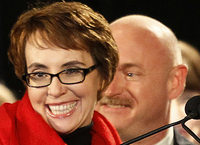 Rep. Gabrielle Giffords, accompanied by her husband, former astronaut Mark Kelly, reacts after leading the Pledge of Allegiance at the start of a memorial vigil on Jan. 8.
