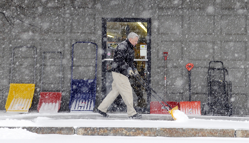 INVENTORY: Bill Harvey shovels snow Thursday from the walk in front of his Gardiner business, Harvey's Hardware. Several inches of snow is forecast.