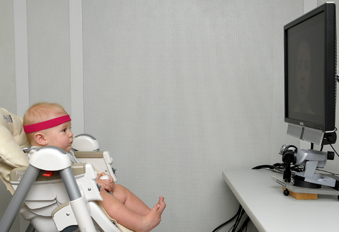 """This undated handout photo provided by Florida Atlantic University shows a baby, looking at a monitor, wearing a band that contains a little magnet that the head-tracker, under the monitor uses to determine head position which, in turn, enables the eye tracker to find the eye and the pupil. New research suggests babies don't learn to talk just from hearing sounds _ they're lip-readers, too. It happens during that magical stage when a baby's babbling gradually changes from gibberish into syllables and eventually into that first """"mama"""" or """"dada."""" (AP Photo/Florida Atlantic University)"""