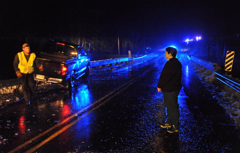 Amity Watts, right, watches as a wrecker pulls her 2008 Dodge Ram from the bridge railing on Unity Road near Benton Friday night. Eight cars were reported to have been off the road with in a quarter mile stretch of road as driving conditions became dangerously icy.